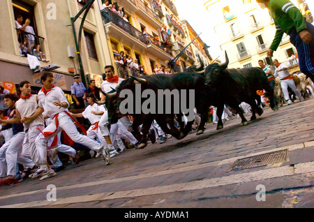 Runners take part in the encierro at Pamplona Spain - Stock Photo