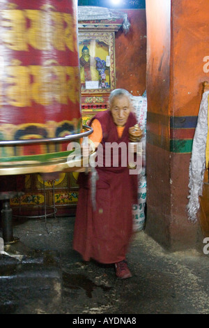 Tibetan priest turning a large prayer wheel in a monastary in Lhasa Tibet - Stock Photo