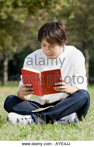 Young man reading in park - Stock Photo
