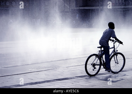 Silhouette of youth boy on bicycle against fountain spray background - Stock Photo