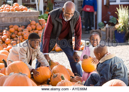 A grandfather and his grandchildren choosing pumpkins - Stock Photo