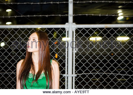 Young woman standing near a wire fence - Stock Photo