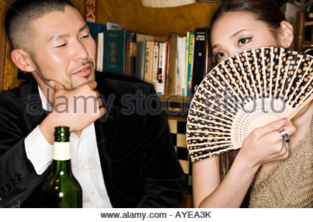 Woman covering her face with a hand fan - Stock Photo