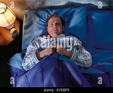 man laying awake in bed not sleeping. - Stock Photo