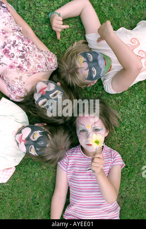 Looking down on four little girls with painted faces  - Stock Photo