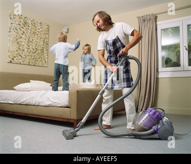 Young father with two young children cleaning bedroom - Stock Photo