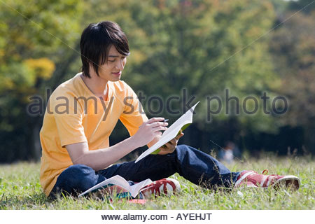 Young man studying in park - Stock Photo