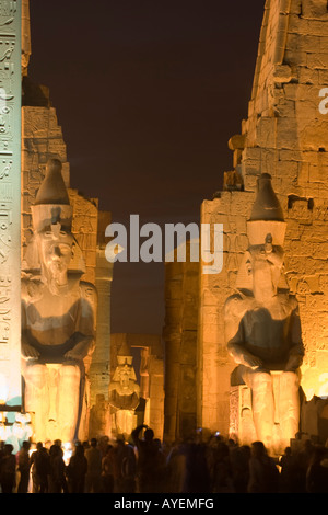 First pylon main entrance with two statues of Ramses II Luxor temple at night Luxor Nile valley Egypt - Stock Photo