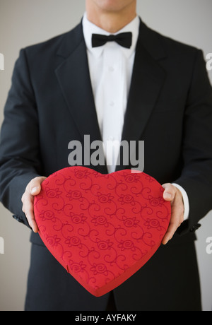 Man in tuxedo holding heart shaped box - Stock Photo