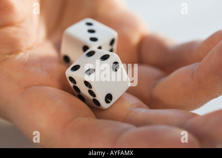 Close up of dice in man's hand - Stock Photo