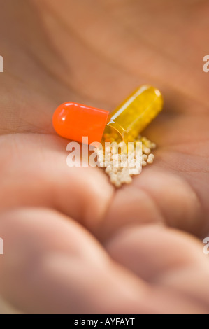 Close up of open medication capsule in man's hand - Stock Photo