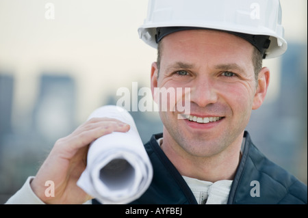 Male construction worker holding blueprints - Stock Photo