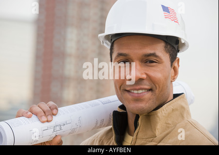 African male construction worker holding blueprints - Stock Photo