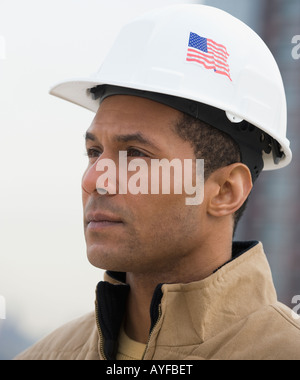 African male construction worker with American flag on hard hat - Stock Photo