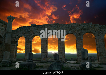 Volubilis Roman ruins Dates from the 2nd and 3rd centuries AD Sunset silhouettes the curved archways of the Basilica - Stock Photo