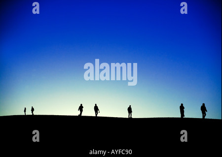 Tourism Tourists on sand dunes in silhouette against the sunrise Erg Chebbi area Sahara desert Morocco - Stock Photo