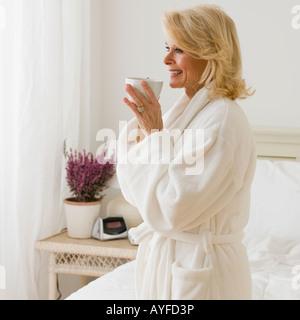 Senior woman in bathrobe drinking coffee - Stock Photo