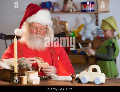 Santa Claus looking at toys - Stock Photo