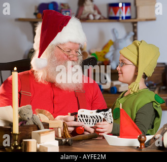 Santa Claus and elf with toys - Stock Photo