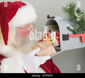 Santa Claus putting gifts in mailbox - Stock Photo