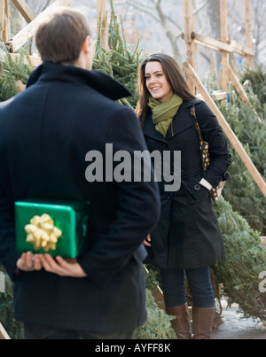 Man surprising girlfriend with gift - Stock Photo