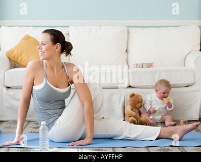 Mother practicing yoga next to baby on floor - Stock Photo