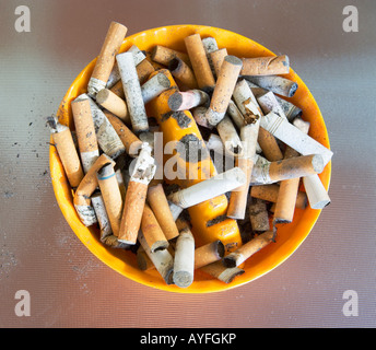 ashtray filled with many cigarette butts - Stock Photo