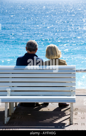 a couple on a bench enjoying sunny afternoon on the beach in Nice, South France - Stock Photo