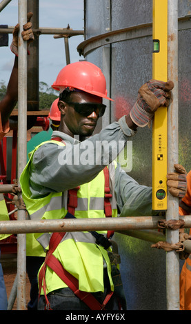 Construction worker using spirit level while putting up scaffolding for water and sewage treatment plant,Ghana, - Stock Photo