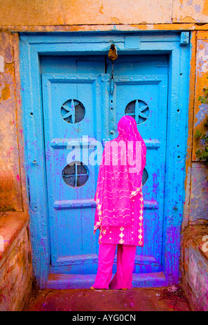 Woman in Old Delhi by a colorful door, India