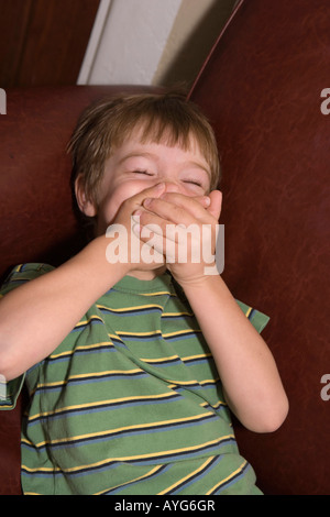 five year old boy covering mouth with both hands, trying not to laugh - Stock Photo