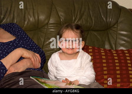 toddler reading book with grandmother happy to be wearing her designer specs number 2671 - Stock Photo