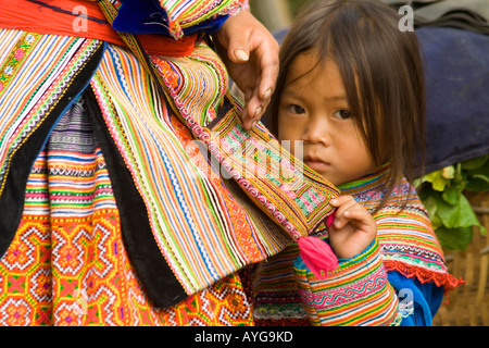 Young Flower Hmong Girl Hides in her Mother s Skirt Bac Ha Market near Sapa Vietnam - Stock Photo