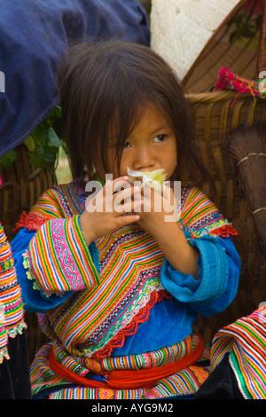 Young Flower Hmong Girl Eating Fruit Bac Ha Market near Sapa Vietnam - Stock Photo
