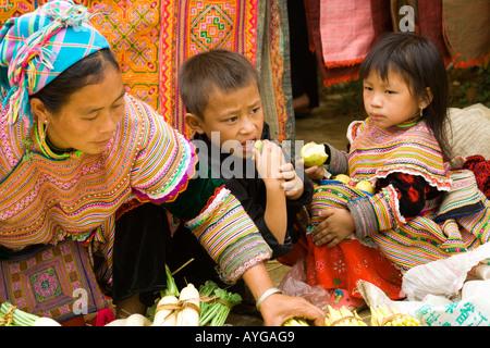 Flower Hmong Children Eating Fruit Bac Ha Market near Sapa Vietnam - Stock Photo