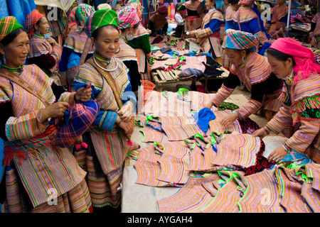 Flower Hmong Women Buy and Sell Colouful Clothing and Fabrics Bac Ha Market near Sapa Vietnam - Stock Photo