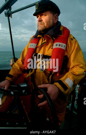 An RNLI coxswain at the helm of a lifeboat off the north devon coast - Stock Photo