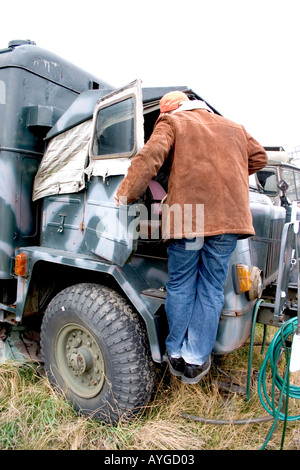 Visitor inspecting cab of military truck on exhibit at site of mock military mess hall. Rawa Mazowiecka Poland - Stock Photo