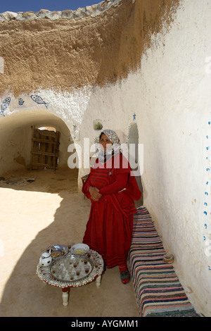Woman in Berber troglodyte underground home takes shelter in shade from fierce heat Matmata Tunisia - Stock Photo