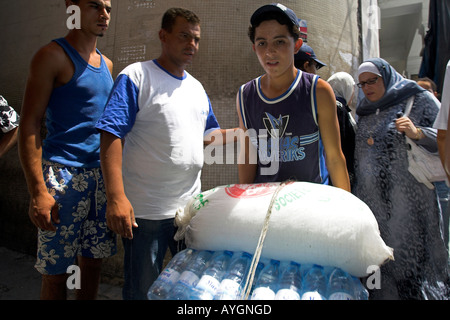 Barrow boy pushing drinking water and crushed ice in narrow lane Medina Tunis Tunisia - Stock Photo