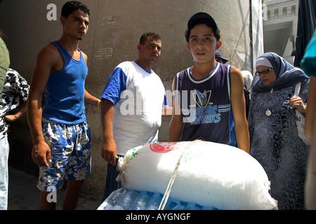 Barrow boy pushing bottles of water and crushed ice in narrow lane Medina Tunis Tunisia - Stock Photo