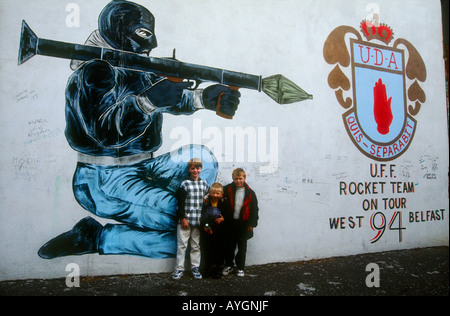children playing amongst Loyalist mural of paramilitary fighters, West Belfast - Stock Photo