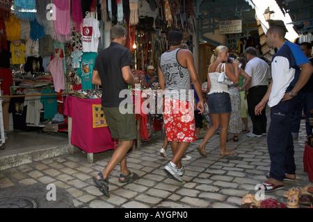 Young visitors walk past stalls in a narrow lane Sousse Medina Tunisia - Stock Photo