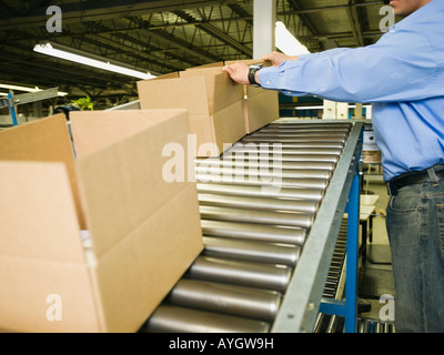 Asian male factory worker checking product - Stock Photo