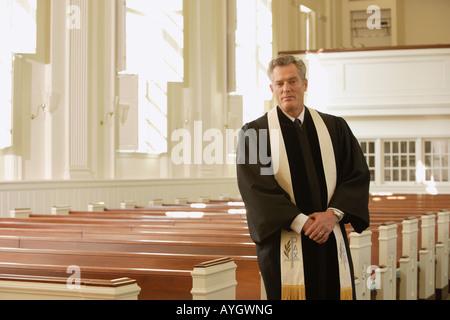 Priest standing next to pews - Stock Photo