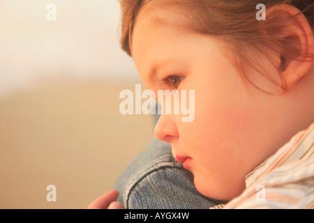 Close up of child resting on parent's shoulder - Stock Photo