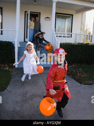Children dressed in Halloween costumes leaving house - Stock Photo