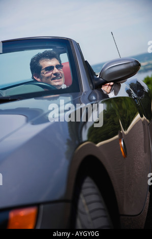 Man driving convertible car - Stock Photo