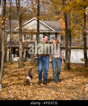 Couple walking dog in woods - Stock Photo