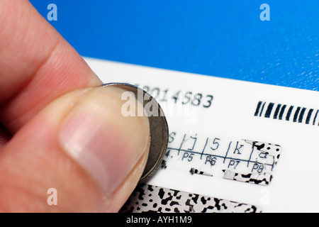 hidden secret number being revealed from scratch off panel using coin - Stock Photo